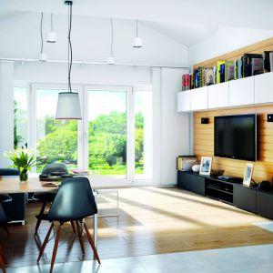 Białe ściany i jasne drewno, w połączeniu z dużymi oknami potęgują wrażenie przestronności salonu. Proj. Dom w nerinach. Fot. Archon +