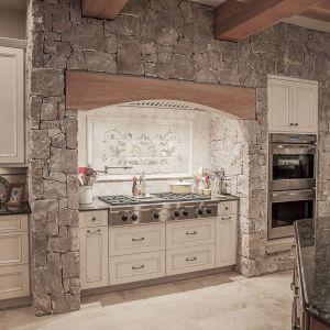 Zabudowa kuchenna znalazła miejsce w wykończonej kamieniem wnęce. Projekt i zdjęcia Kelly & Stone Architects