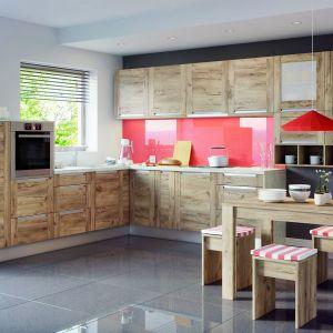 Czerwień w postaci kolorowego szkła na ścianie nad blatem sprawia, że kuchnia Olivia Soft z frontami w dekorze dąb złoty nie jest monotonna. Fot. KAM