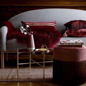 Bawełniana poduszka z frędzlami w kolorze burgundowym sprawdzi się jako stylowy dodatek do każdej kanapy lub fotela. Fot. Bloomingville