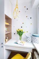 Pamiętajmy, że decydujący wpływ na ostateczny charakter wnętrza mają dodatki. Postawiliśmy na różne odcienie żółci oraz szarości. Żółte krzesło, kable żarówek, musztardowy pompon, chorągiewki, szaro-żółtą pościel czy dywan. Świetnie pasują do tego naklejki nad biurkiem tzw. konfetti Dekornik. Właścicielka pokoju lubi mieć pod ręką drobne skarby, dlatego chowa je do okrągłych, nakrapianych pojemników Done by Deer, dostępnych w Fabryka Form.