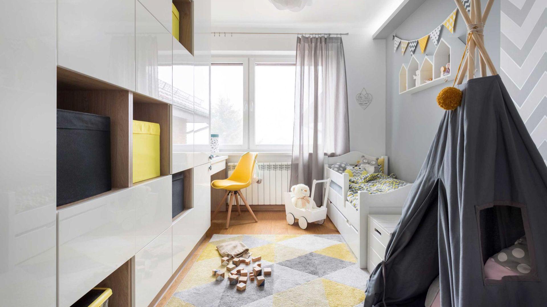 Projektantka pamiętała, że decydujący wpływ na ostateczny charakter wnętrza mają dodatki. Postawiła na różne odcienie żółci oraz szarości: żółte krzesło, kable żarówek, musztardowy pompon, chorągiewki, szaro-żółtą pościel czy dywan. Projekt i zdjęcia: Kamila Snela / Wnętrzomania