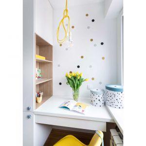 Z żółtymi dodatkami świetnie współgrają naklejki nad biurkiem i okrągłe, nakrapiane pojemniki, w których właścicielka pokoju chowa drobne swoje skarby.Projekt i zdjęcia: Kamila Snela / Wnętrzomania