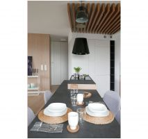 Kuchenny półwysep płynnie przechodzi w stół oraz widoczną od strony salonu szafkę. Zdjęcia: Biuro Architektoniczne ArchOMEGA