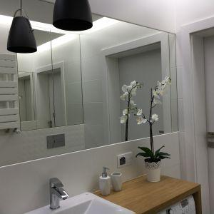Łazienka w bloku w nowo wybudowanym osiedlu Czarneckiego w Poznaniu to proste, przestronne pomieszczenie z kabiną, umywalką blatową oraz pralką, której praktycznie nie widać. Fot. Luxrad