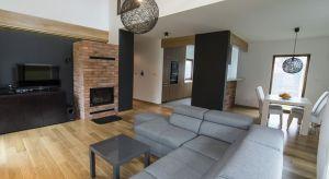 Wnętrze tego nowoczesnego domu jednorodzinnego pozbawione jest zbędnych detali, wręcz surowe. Główny motyw dekoracyjny stanowi cegła, zestawiona z ciepłym, drewnianym fornirem.