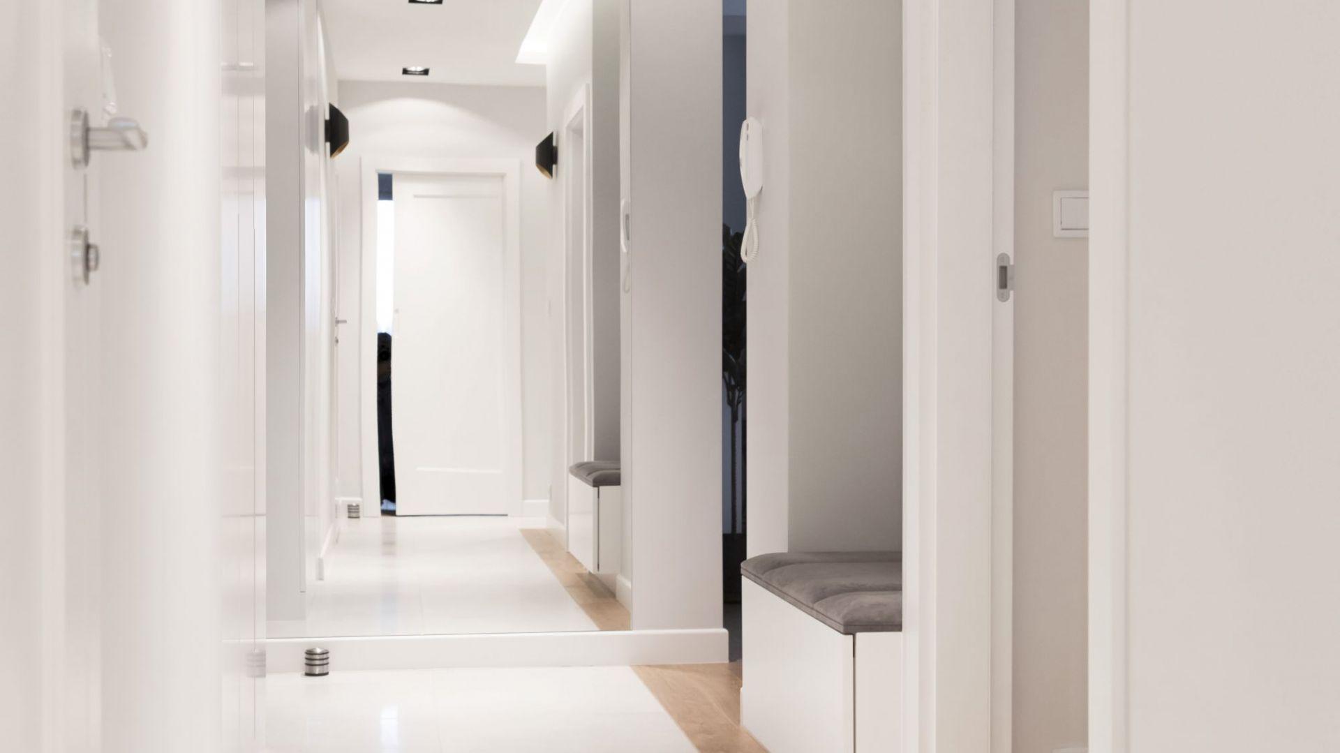 Do poszerzonego przedpokoju można było wstawić zrobione na wymiar pojemne szafy, na czym bardzo zależało gospodarzom. We wnęce – tapicerowana ławeczka ze schowkiem na buty pod siedziskiem. Projekt i zdjęcia: Małgorzata Górska-Niwińska/Pracownia Architektoniczna MGN