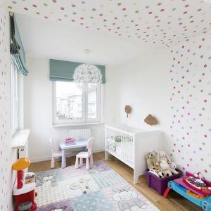 W pokoju córeczki gospodarzy uwagę zwraca wesoła tapeta w kolorowe groszki, którą oklejono nie tylko fragmenty ścian, ale i część sufitu. Projekt i zdjęcia: Małgorzata Górska-Niwińska/Pracownia Architektoniczna MGN