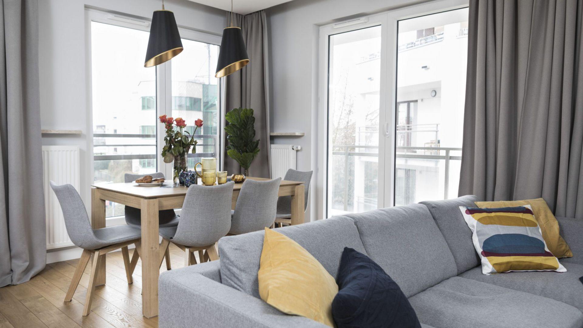 W salonie połączonym z kuchnią mieści się przestronna część dzienna ze strefami o różnej funkcji, których odrębność podkreśla między innymi przemyślane ustawienie mebli. Projekt i zdjęcia: Małgorzata Górska-Niwińska/Pracownia Architektoniczna MGN