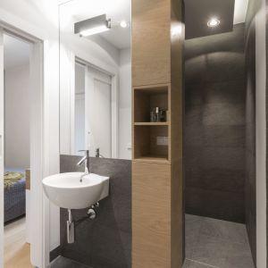 Łazienka po połączeniu z garderobą stała się bardzo przestronna. Znajduje się w niej obszerna kabina prysznicowa bez brodzika, umywalka, sedes i dwa pojemne schowki. Projekt i zdjęcia: Małgorzata Górska-Niwińska/Pracownia Architektoniczna MGN
