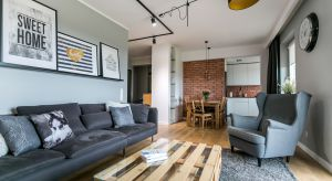Inwestorzy - młode małżeństwo, to zwolennicy stylu nowoczesnego z mocnymi akcentami industrialnymi oraz elementami retro. Na ścianie w kuchni, w salonie oraz w jadalni zastosowano płytki imitujące starą cegłę. W aranżacji mieszkania wykorzystan