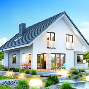 Dwuspadowy dach i ciekawe uzupełnienie tynu płytkami imitującymi kamień, nadają bryle domu ciekawego charakteru. Dom w Zdrojówkach. Fot. Archon +