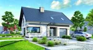 Dom w Zdrojówkach to interesujący projekt małego domu z poddaszem użytkowym o powierzchni 110 mkw. Jego nowoczesny styl podkreśla jasne i lekkie wykończenie elewacji oraz narożne przeszklenie w salonie.
