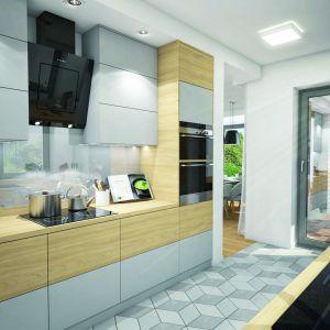 W częściowo zamkniętej kuchni można zaaranżować wygodną przestrzeń do pracy, z równoległym układem szafek. Jej funkcjonalność podnosi spiżarnia. Dom w Zdrojówkach. Fot. Archon +