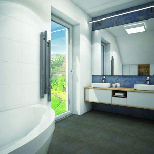 Spore okno i duże lustro optycznie powiększa wnętrze łazienki. Dom w Zdrojówkach. Fot. Archon +