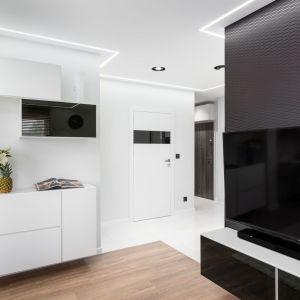 Ścianę za telewizorem wykończono czarną tapetą z metalicznym wzorem. Projekt: Estera i Robert Sosnowscy / Studio Projekt. Zdjęcia: Fotomohito