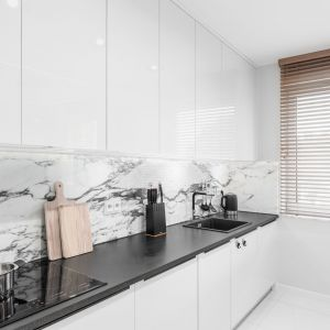 Przestrzeń nad kuchennym blatem roboczym pokrywa czarno biały marmur. Projekt: Estera i Robert Sosnowscy / Studio Projekt. Zdjęcia: Fotomohito