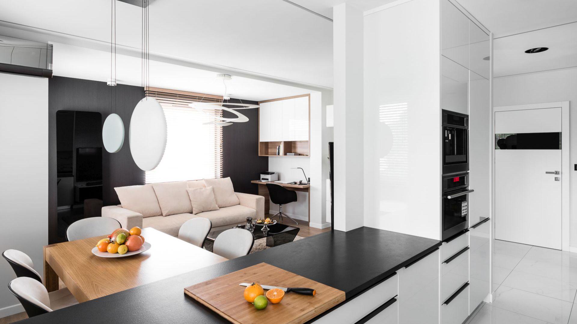 Po wyburzeniu ściany między salonem a kuchnią powstała otwarta strefa dzienna. Projekt: Estera i Robert Sosnowscy / Studio Projekt. Zdjęcia: Fotomohito