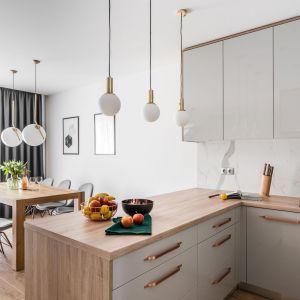Otwarta kuchnia błyszczy, dzięki miedzianym uchwytom mebli. Projekt: Estera i Robert Sosnowscy / Studio Projekt. Zdjęcia: Fotomohito