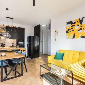 Wyrazista żółta kanapa i obraz w tych samych odcieniach stanowią ciekawą dekorację tego wnętrza. Projekt: arch. Karolina Karwowska. Fot. Michał Młynarczyk