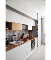Funkcjonalnie rozwiązana zabudowa kuchenna przeplata się z domowym biurem,  które jednym ruchem ręki może zniknąć za specjalnymi drzwiami pozostawiając jedynie gładką płaszczyznę minimalistycznego mebla. Projekt i zdjęcia: Dominika Wojciechowska / NIDUS interiors
