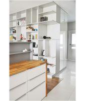 Specjalnie zaprojektowana pojemna szafa z przedpokoju (subtelnie oddzielająca drzwi do prywatnej łazienki) niewidocznie łączy się z efektowną biblioteką w salonie. Projekt i zdjęcia: Dominika Wojciechowska / NIDUS interiors