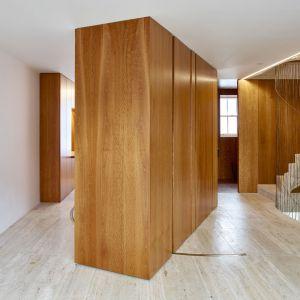 Wysokie regały, sięgające od podłogi aż po sufit, są ruchome i wyposażone w ukryte drzwi przesuwne, które na co dzień służą do przedzielania części piętra i tworzenia osobnego pokoju. Projekt i zdjęcia: Amin Taha Architects