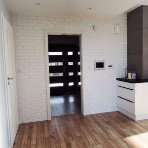 Parter domu tworzą: hol wejściowy oraz klatka schodowa, salon z kuchnią i jadalnią, łazienka dla gości, pokój biurowy. Projekt: Agnieszka Noworzyń (pracownia i-2)