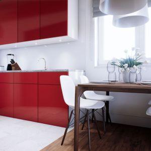 Jasne wnętrze ożywia wyrazista czerwień szafek kuchennych. Dom Mini 3. Fot. Pracownia Projektowa Archipelag