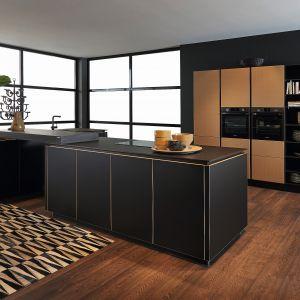 Minimalistyczna kuchnia Flair dostępne w ofercie firmy Nolte Küchen idealnie sprawdzi się we wnętrzach otwartych. Fronty wysokiej zabudowy z jednym słupkiem otwartych półek zdobi fornir. Całość uzupełnia praktyczna wyspa z wykończeniu czarny mat. Fot. Nolte Küchen