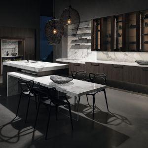 Kuchnia Lano dostępna w ofercie firmy Rational to połączenie klasycznej elegancji ubranej w ciemne drewno z modnym marmurem Carrara. Otwarte półki z przeszkleniami oraz zintegrowany z wyspą stół podkreślają jej salonowy charakter. Fot. Rational