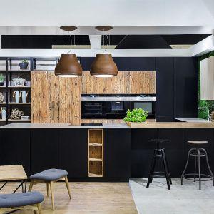 Meble kuchenne Josse dostępne w ofercie firmy Vigo. Ciepłe drewno w zestawieniu z czernią lakierowanych satynowych frontów, połączone zostało z soczystą zielenią paneli ściennych z mchu, cegłą oraz kamiennym blatem. Fot. Vigo Meble