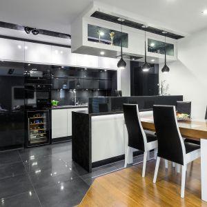 Otwarta na salon kuchnia urządzona została w nowoczesnym, minimalistycznym stylu. Postawiono tu na klasyczny duet barw - czerń i biel. Fot. Studio Kuchenne A&K