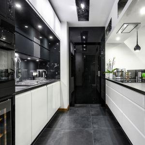 Lakierowanego na wysoki połysk fronty oraz elementy szklane dodają kuchni blasku. Funkcjonalność zapewnia dwurzędowa zabudowa z półwyspem. Fot. Studio Kuchenne A&K