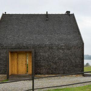 Głównym materiałem zastosowanym w całości projektu jest drewno. Dach oraz fasada budynku zostały pokryte wiórem osikowym. Drewniane drzwi wejściowe udekorowano ornamentem nawiązującym do lokalnej tradycji. Projekt i zdjęcia: Monika i Adam Bronikowscy, Grupa Projektowea HOLA