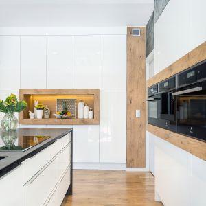 Fronty z lakierowanego MDF-u połączone zostały z naturalnymi materiałami jak granit matrix i fornir kamienny, które dodają kuchni szlachetnej elegancji. Fot. Studio Kuchenne A&K
