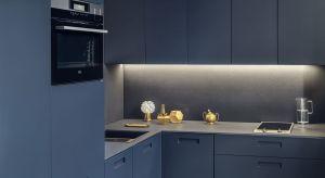 Niewielka kuchnia w ciemnych kolorach nie jest dla wielu osób oczywistym wyborem. W przypadku tej realizacji za takim rozwiązaniem stanęła duża ilość światła wpadającego przez okno, otwarty charakter pomieszczenia i sufit o wysokości niemal 3,5