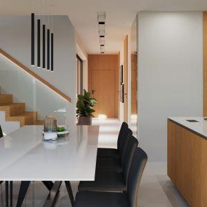 Otwarta kuchnia została połączona z jadalnią i oddzielona od niej praktycznym półwyspem. Dom HomeKONCEPT 49. Fot. HomeKONCEPT
