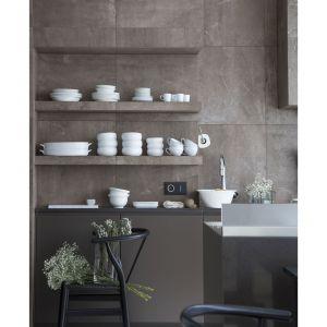Do pokrycia ścian i okapu architekci wykorzystali płytki gresowe imitujące kamień. Projekt: Studio.O. Fot. Aga Kobus