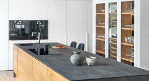 Prezentowanakompozycja wykonana została na indywidualne zamówienie. Dzięki zastosowanym materiałom kuchnia estetycznie łączy się z salonem, a meble idealnie dopasowane są do układu pomieszania.