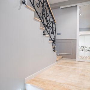 Na schodach zastosowano marmur korespondujący kolorystycznie z imitującą drewno płytką na podłodze w salonie. Projekt: Marta Sergiej. Fot. Wojciech Dziadosz