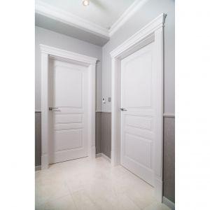 Stolarka drzwiowa z ozdobnymi opaskami dodatkowo podkreśla klasyczny charakter wnętrza. Projekt: Marta Sergiej. Fot. Wojciech Dziadosz