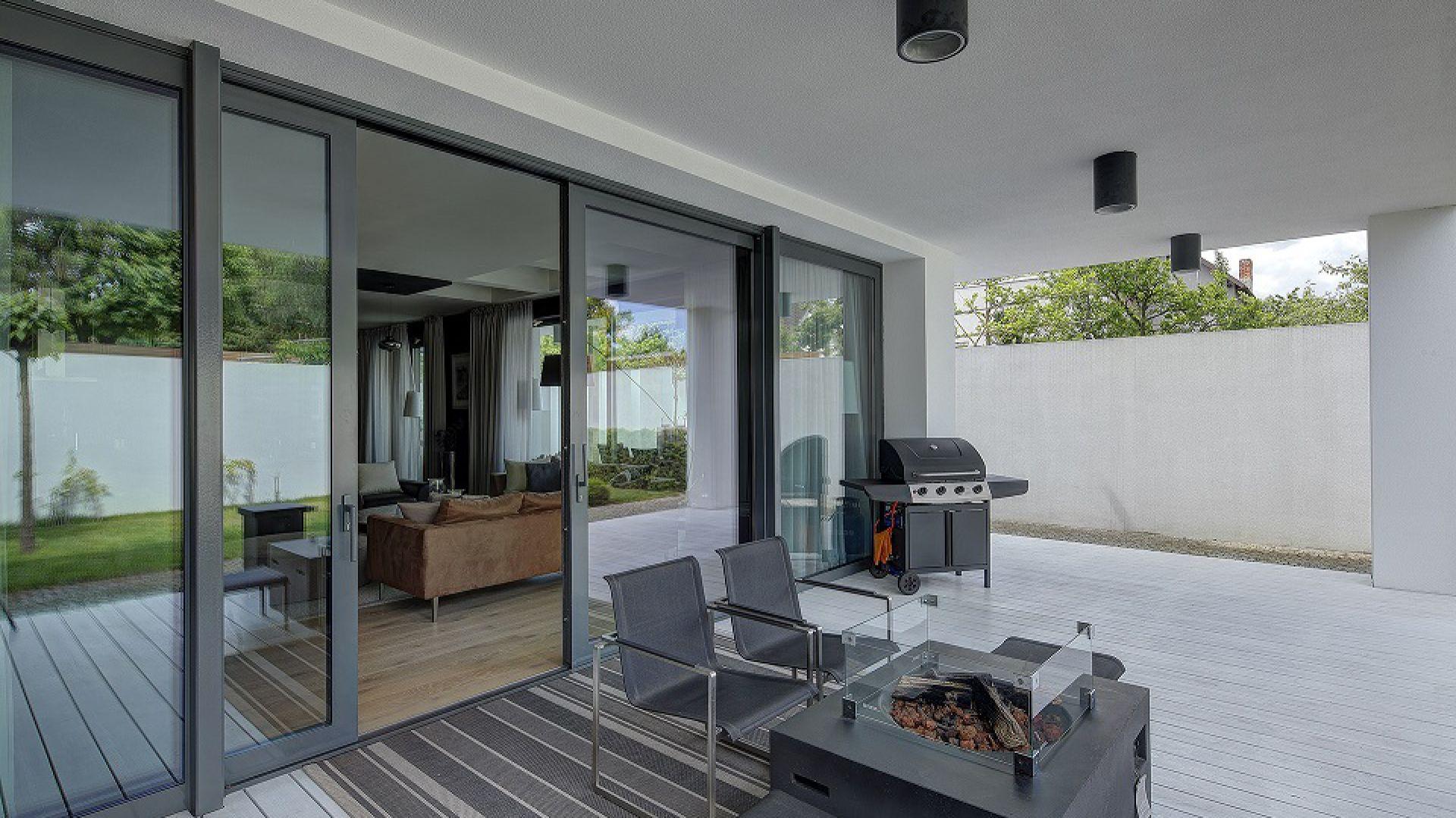 Drzwi podnoszono-przesuwne Patio HST mogą mieć nawet 6 metrów szerokości w wersji PVC i aż 12 metrów w wersji aluminiowej. Komfortowe w użytkowaniu, zapewniają znakomitą izolację termiczną i akustyczną. A do tego wyposażone są w mechanizmy antywłamaniowe. Dzięki nim możemy otworzyć nasz dom na ogród czy taras i cieszyć się letnimi wieczorami w towarzystwie przyjaciół, lub przy dobrej lekturze. Fot. MS więcej niż OKNA
