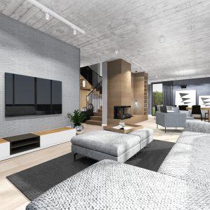Otwarta przestrzeń dzienna to: strefa rodzinna z dużą sofą i TV, strefa przy kominku do czytania lub indywidualnego relaksu i strefa jadalni. Projekt: TWORZYWO studio. Fot. TWORZYWO studio