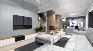 Nowoczesny układ domu od razu podpowiedział architektom, w jakim estetycznym kierunku iść. Duże i wysokie przestrzenie, wylewany betonowy strop i szerokie przejścia to największe, lecz nie jedyne atuty budynku.