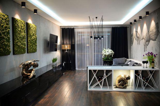 Zaaranżowana na planie prostokąta przestrzeń łączy funkcje salonu, kuchni i jadalni. Zamysłem projektantki było połączenie ascetycznej nowoczesności z nutą klasycznej elegancji.