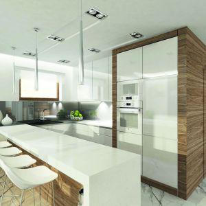 """Kuchnia jest tylko częściowo otwarta na jadalnię. Obie strefy rozdziela bar śniadaniowy z białym blatem i drewnianym wykończeniem. Biała zabudowa kuchenna na jednej ze ścian została """"zakuta w drewno"""", co doskonale koresponduje ze stylistyką salonu. Dom Amarylis 2. Projekt: arch. Tomasz Sobieszuk. Fot. Domy w Stylu"""