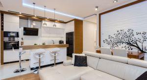 Łączna powierzchnia salonu i kuchni wynosi 25m². Właściciele lubią gotować i dlatego zależało im na dużej kuchni z wyspą. Pragnęli też mieć stół, który pomieści całą rodzinę.
