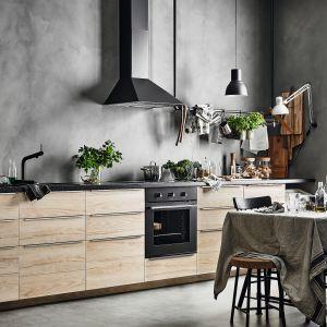 Kuchnia łączy naturalne elementy takie jak drewno, rośliny i len z eleganckimi, prostymi liniami i industrialnymi fakturami, takimi jak beton. Szarości i czernie, dzięki jasnym frontom z imitacji drewna jesionowego, nie przytłaczają pomieszczenia. Meble dostępne w ofercie IKEA. Fot. IKEA