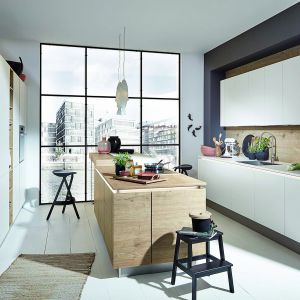 Meble Timber/Feel, które łączą biel z pięknym, dębowym fornirem. Prosty podział frontów uwypukla niepowtarzalny rysunek drewna, tworząc klimatyczną, a przy tym nowoczesną przestrzeń. Dostępne w ofercie firmy Nolte Küchen. Fot. Nolte Küchen